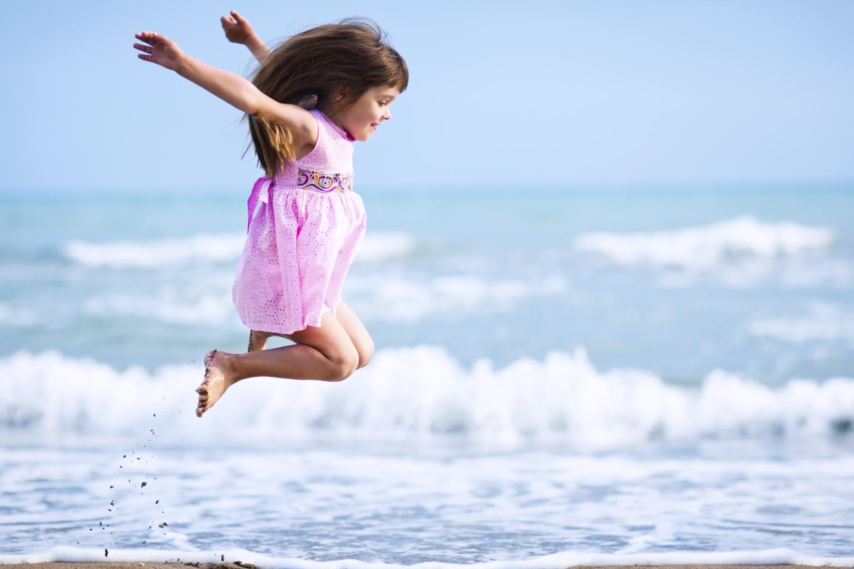 Pige der springer ved havet